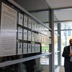 ECpE Chair Ashfaq Khokhar poses beside the new wall for the Hall of Fame