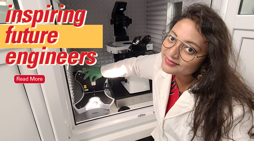 Image text: Inspiring Future Engineers. Read More. Photo shows faculty member Anwesha Sarkar in a lab coat and glasses using a microscope in a lab setting.