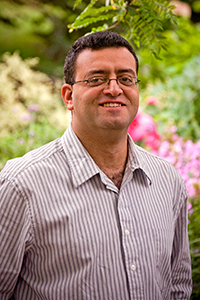Headshot photo of Mohamed Mokbel standing outside with trees and flowers in the background
